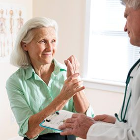 A doctor listens to a senior woman patient describe wrist pain. See my portfolio for more in this series.